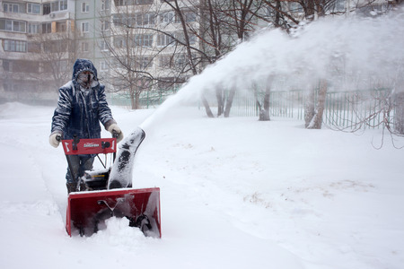 ice cold: KHABAROVSK, RUSSIA - DECEMBER 03, 2015: A man removing snow with a snowblower during snowstorm