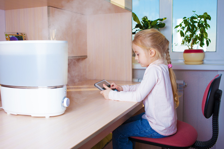 humidify: Little girl with tablet pc sitting at the table near humidifier