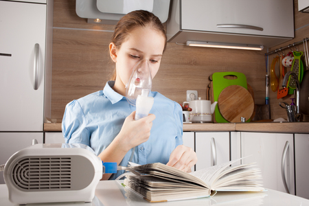 Cute girl doing inhalation and reading book in the kitchen