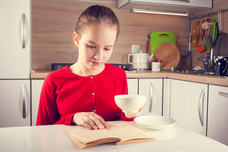 kid book: Teenage girl reading book with a cup of tea at the kitchen Stock Photo