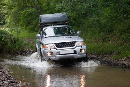 far off: BOLSHOY KAMEN, RUSSIA - AUGUST 03, 2015: SUV is crossing a small river