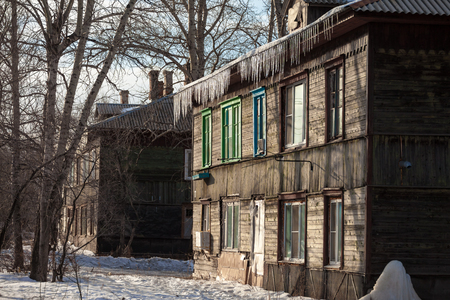 ruberoid: Icicles hanging down from the roof of an old house