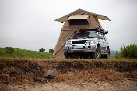 encampment: ZARUBINO, RUSSIA - JULY 21, 2015: A car with rooftop tent on sea coast Editorial