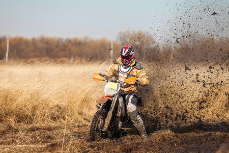 skids: Enduro bike rider on a field with dry grass in autumn. The motorcycle skids and makes a lot of mud splashes Stock Photo