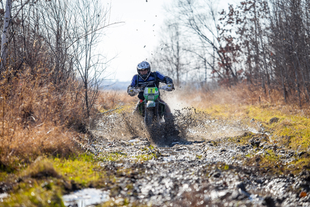 skids: KHABAROVSK, RUSSIA - OCTOBER 23, 2016: Enduro bike rider on a dirt road. The motorcycle skids and makes a lot of mud splashes
