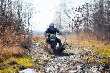 KHABAROVSK, RUSSIA - OCTOBER 23, 2016: Enduro bike rider on a dirt road. The motorcycle skids and makes a lot of mud splashes