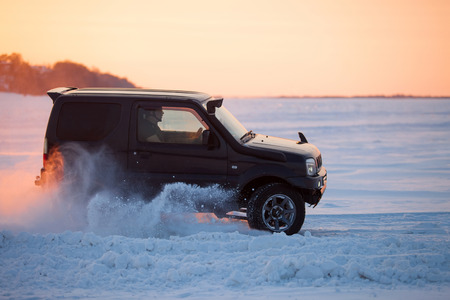 KHABAROVSK, RUSSIA - JANUARY 28, 2017: Suzuki Jimny moving on ice of a frosn river at sunset