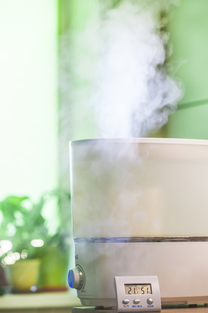 hygrometer: Vapor from humidifier in front of window and nygrometer in front of it Stock Photo