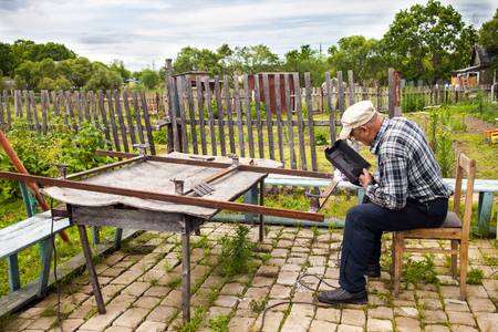 fireproof: Aged man welding metal structure at his dacha Stock Photo