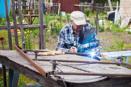 dacha: Elderly man welding metal structure at the garden