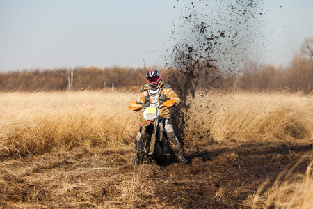 skids: Enduro bike rider in a field with dry grass in autumn. The motorcycle skids and makes a lot of mud splashes Stock Photo