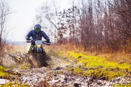 Enduro bike rider on dirt track with deep mud