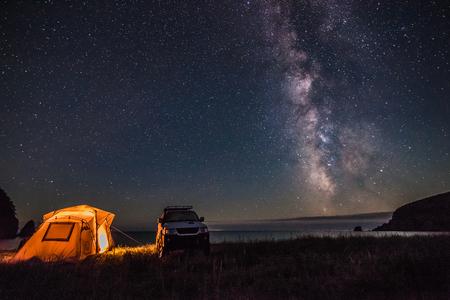 観光客が天の川で夜の海岸を海でキャンプします。ヒュー ・ iso からいくつかのノイズが存在します。 写真素材