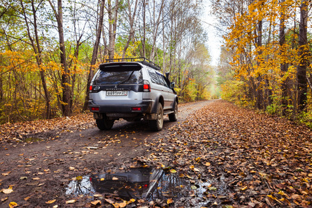 KHABAROVSK, RUSSIA - SEPTEMBER 16, 2017: Mitsubishi Pajero Sport on dirt road in autumn forest