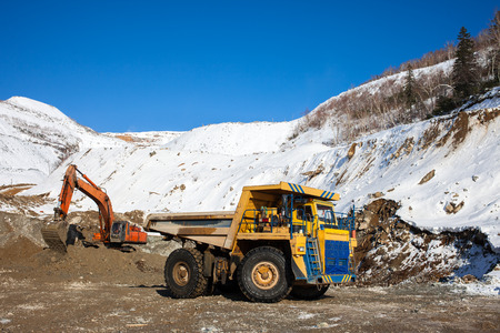 Excavator loading dump truck at gold mining