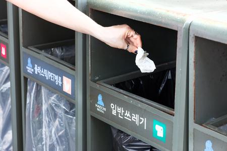 SEOUL, KOREA - APRIL 28, 2015: Woman throwing paper napkin into special trash can Standard-Bild - 110497859