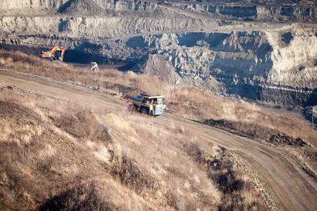Yellow dump truck moving by the road to coal mine Standard-Bild - 102770071
