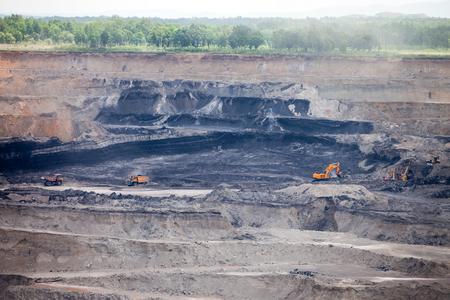 Dump trucks and excavator working at coal mine Standard-Bild - 103874428