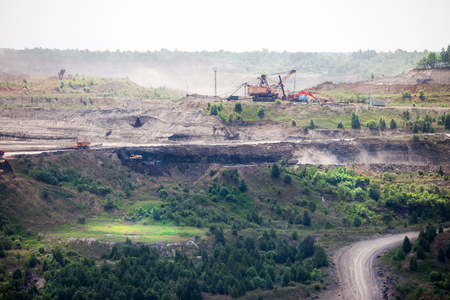 Dump trucks and excavators working at open coal mine Standard-Bild - 103874430