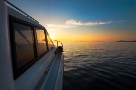 White motorboat moving to sunset Standard-Bild - 110545360