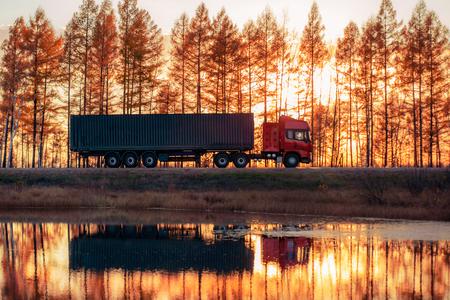 Roter LKW auf einer Straße bei Sonnenuntergang. Fokus auf Container Standard-Bild