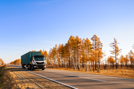 White semi-truck with container on autumn road Standard-Bild - 110545634