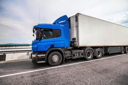 Blue truck on a road with refrigerator trailer Standard-Bild - 121097936