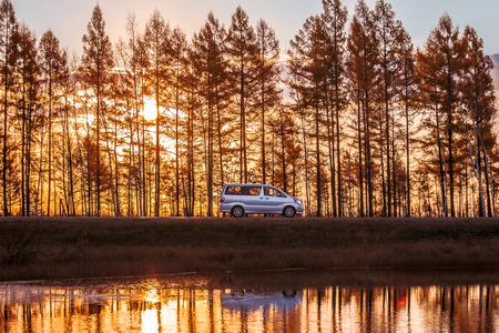 Silver minivan on foreat road near a lake at sunset Standard-Bild - 121097937
