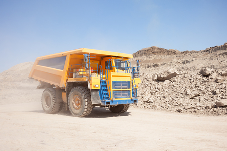 Yellow dump truck moving in a coal mine