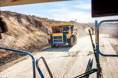 Yellow dump truck moving in a coal mine. View from another truck Фото со стока