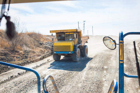 Old yellow dump truck moving in a coal mine. View from another truck
