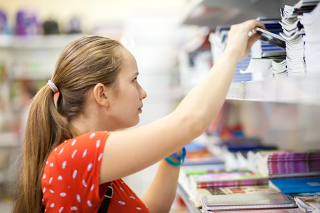 Teenage girl is choosing copybook in a bookshop