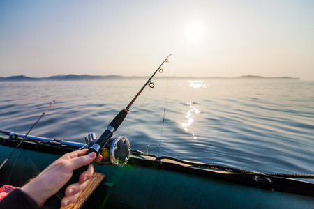 Fish-rod in fishermens hand. Fishing  at inflatable boat