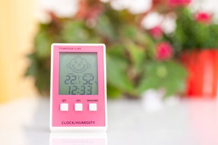 Pink hygrometer on white table with home plants on the background Фото со стока
