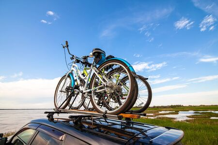 Three bicycles on roof racks at the river bank