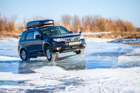 Khabarovsk, Russia - January 4, 2020: Subaru Forester at frozen lake ice. Ice waves