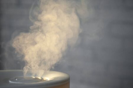 Humidifier spreading steam with white brick wall background. Loft style.