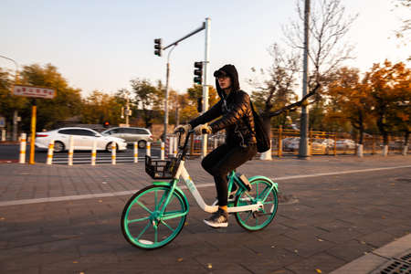 Beijing, China - November 12, 2019: Girl rides rent bicycle at Beijing street in the morning