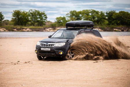 Nikolaevka, Russia - June 23, 2020: Black Subaru Forester moving on sand beach, sand flying from under the wheels