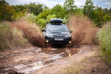 Nikolaevka, Russia - June 23, 2020: Black Subaru Forester moving at dirty forest road making a lot of water splashes