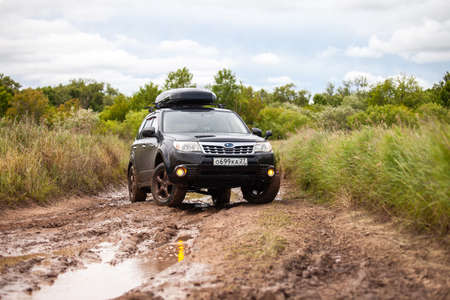 Nikolaevka, Russia - June 23, 2020: Black Subaru Forester at dirty forest road in summer
