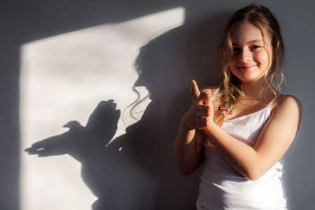 Girl shows dove symbol on the wall that she folded with her hands