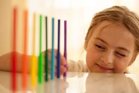 Little girl sets colorful felt pens in a row in rainbow sequence Stok Fotoğraf