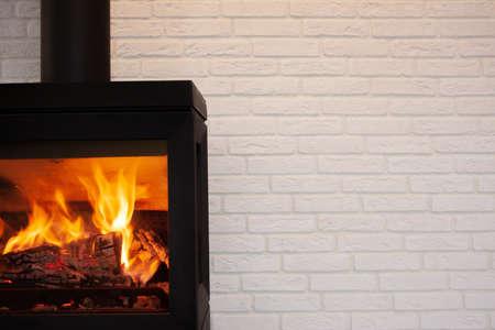 Moderm style cast iron fireplace with white brick background