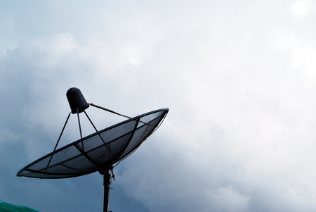 The satellite dish is black with a dark sky before it rains.