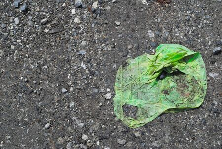 The green plastic bag was blown to the parking lot and was hit by a car. Stock Photo