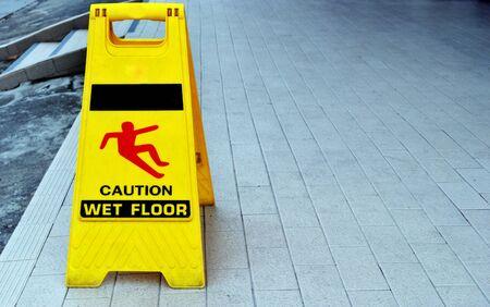 Gelbes Warnschild, das besagt, dass der Boden rutschig ist.