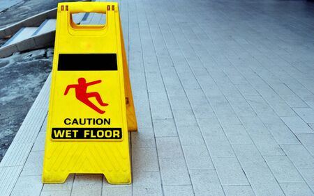 Yellow warning sign that says that the floor is slippery.