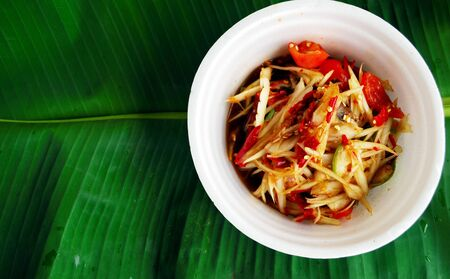Beautiful colorful papaya salad in a cup made of foam, placed on banana leaves. 版權商用圖片