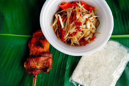 Grilled chicken, sticky rice, papaya salad in a cup made from foam, placed on banana leaves
